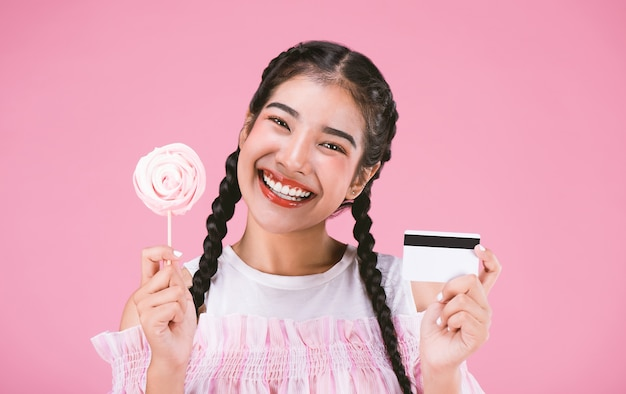 Gelukkig jong meisje dat creditcard met suikergoed over roze achtergrond toont