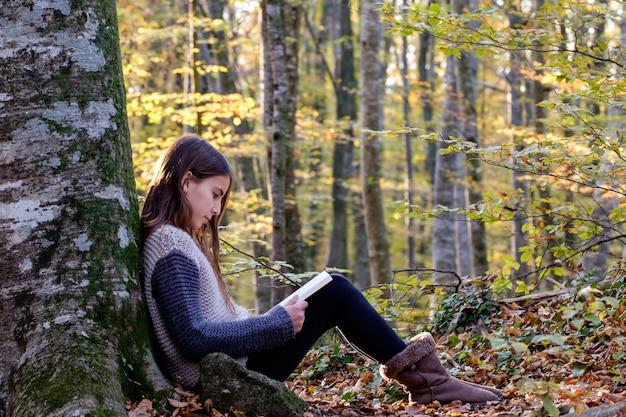 Gelukkig jong meisje dat een boek in de herfstbos leest