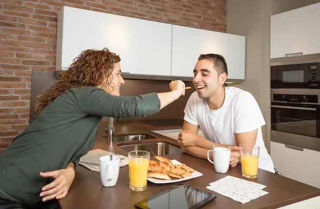 Gelukkig jong meisje dat haar vriendje voedt met een koekje in het weekend thuisontbijt