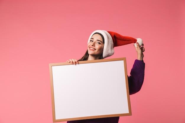 Gelukkig jong meisje dat rode santahoed draagt die zich geïsoleerd over roze bevindt, leeg bord toont
