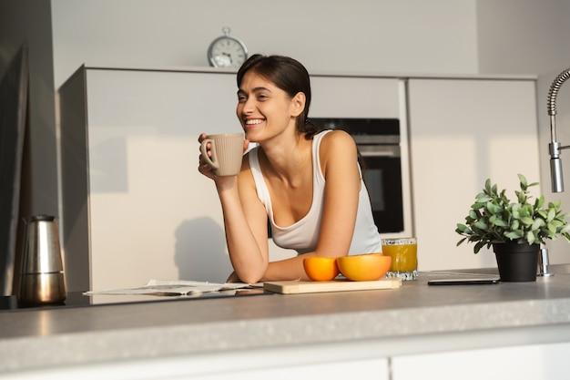 Gelukkig jong meisje dat 's ochtends bij de keuken staat, met een kopje koffie