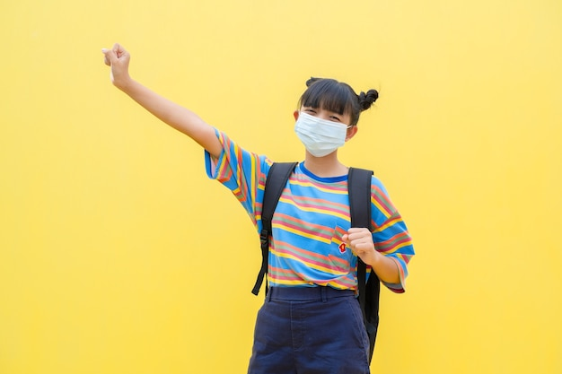 Gelukkig jong meisje draagt een masker zittend op een gele achtergrond
