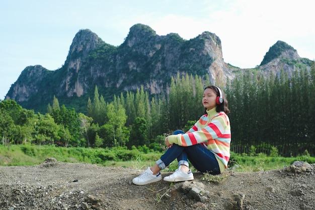 Gelukkig jong meisje draagt een trui die naar muziek luistert terwijl ze op een prachtig landschapsbeeld zit.