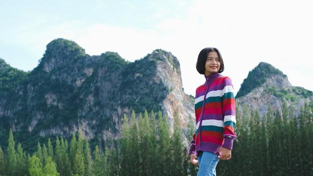 Gelukkig jong meisje draagt een trui die staat met een prachtig uitzicht op het landschap.
