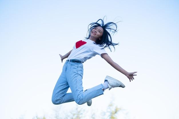 Gelukkig jong meisje draagt een wit overhemd en jean met rood hart springen met hemelachtergrond.