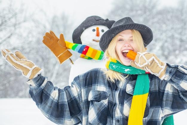 Gelukkig jong meisje eet een wortel in de buurt van een sneeuwpop buitenshuis
