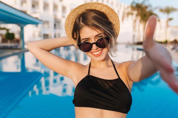 Gelukkig jong meisje glimlachend en nemen selfie, dragen zwarte zwembroek, stijlvolle zonnebril, strooien hoed poseren in de buurt van zwembad in luxehotel, resort, op vakantie, vakantie, zomer.