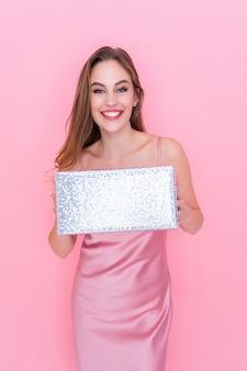 Gelukkig jong meisje glimlachende jurk over geïsoleerde roze achtergrond terwijl ze een feest van de geschenkdoos houdt