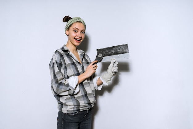 Gelukkig jong meisje in een geruit hemd met een spatel, reparaties aan het doen in haar nieuwe appartement