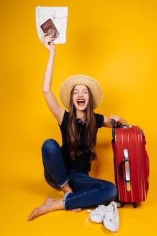 Gelukkig jong meisje in een hoed vliegt op vakantie, houdt een paspoort en kaartjes, een grote koffer met dingen