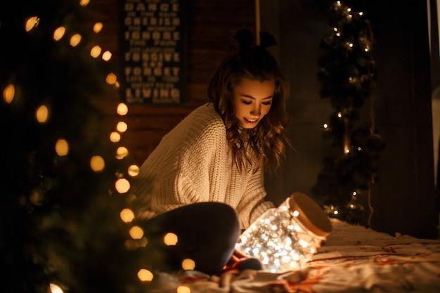 Gelukkig jong meisje in een vintage gebreide trui houdt een magische pot met feestelijke lampjes op het bed