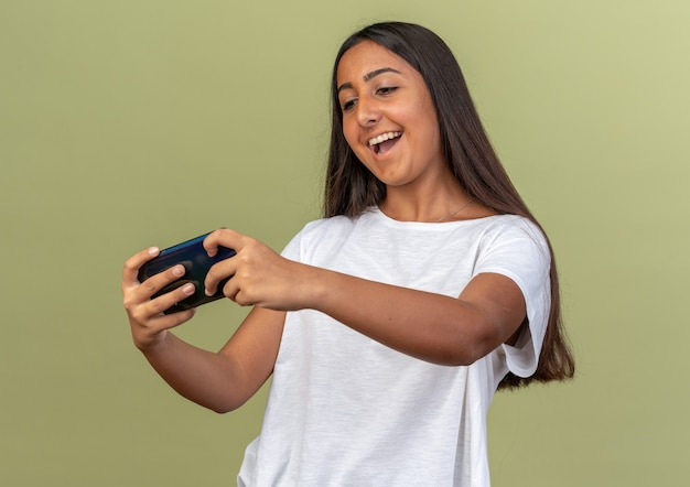 Gelukkig jong meisje in een wit t-shirt dat lacht om spelletjes te spelen met een smartphone die over groen staat