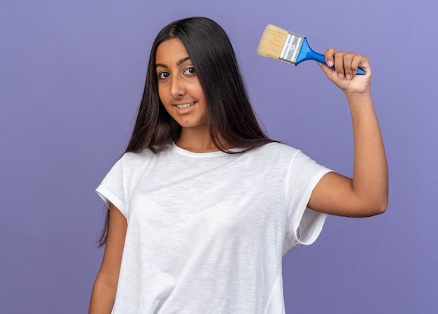 Gelukkig jong meisje in een wit t-shirt met een verfkwast die naar een camera kijkt die vrolijk over blauw staat te glimlachen