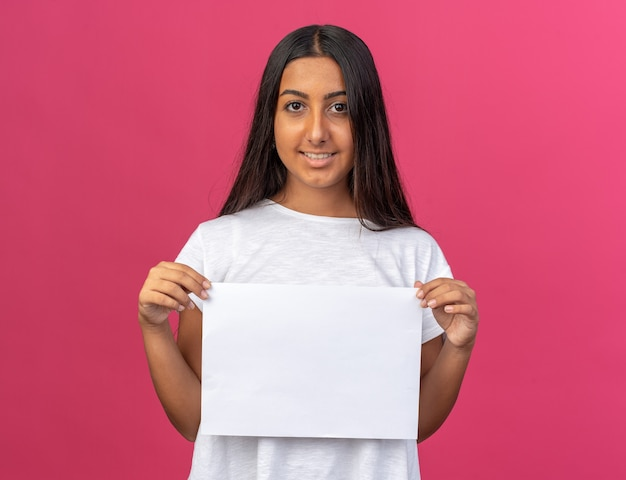 Gelukkig jong meisje in een wit t-shirt met een wit blanco vel papier dat vrolijk naar de camera kijkt