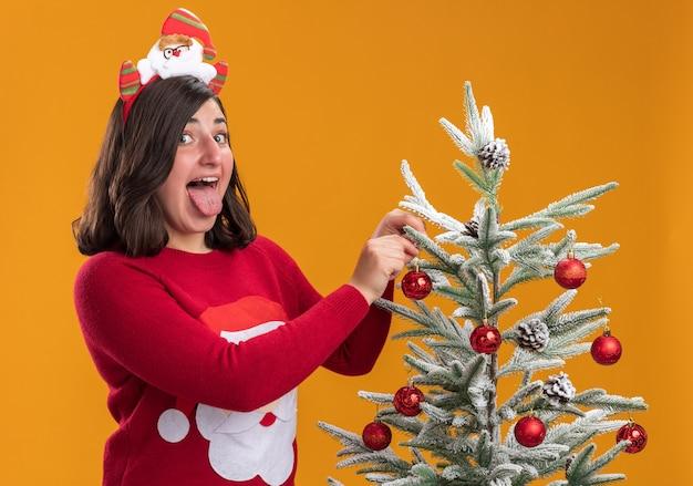 Gelukkig jong meisje in kerst trui met grappige hoofdband tong uitsteekt staande naast een kerstboom opknoping kerstballen erop over oranje muur