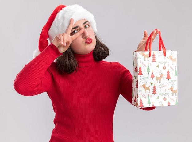 Gelukkig jong meisje in rode trui en kerstmuts met kleurrijke papieren zak met kerstcadeaus met v-teken in de buurt van oog staande over witte muur