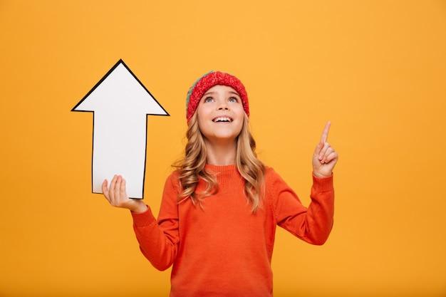 Gelukkig jong meisje in sweater en hoedenholdingsdocument pijl terwijl het richten en het kijken omhoog over sinaasappel