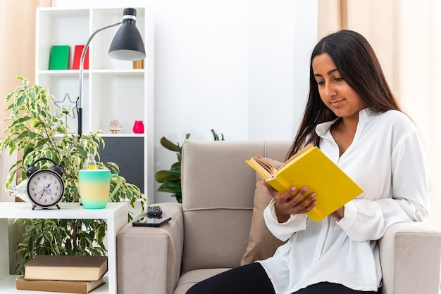 Gelukkig jong meisje in wit overhemd en zwarte broek met boeklezing zittend op de stoel in lichte woonkamer
