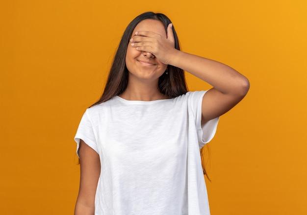 Gelukkig jong meisje in wit t-shirt dat ogen bedekt met hand die vrolijk lacht over oranje achtergrond
