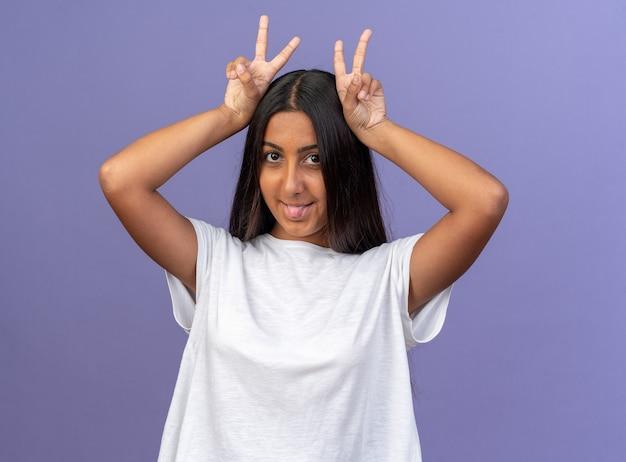 Gelukkig jong meisje in wit t-shirt kijkend naar camera gelukkig en vrolijk imiteert hertenhoorns die tong uitsteken die over blauw staat