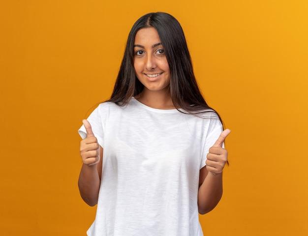 Gelukkig jong meisje in wit t-shirt kijkend naar camera glimlachend zelfverzekerd met duimen omhoog staande over oranje achtergrond