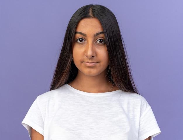 Gelukkig jong meisje in wit t-shirt kijkend naar camera glimlachend zelfverzekerd over blauwe achtergrond