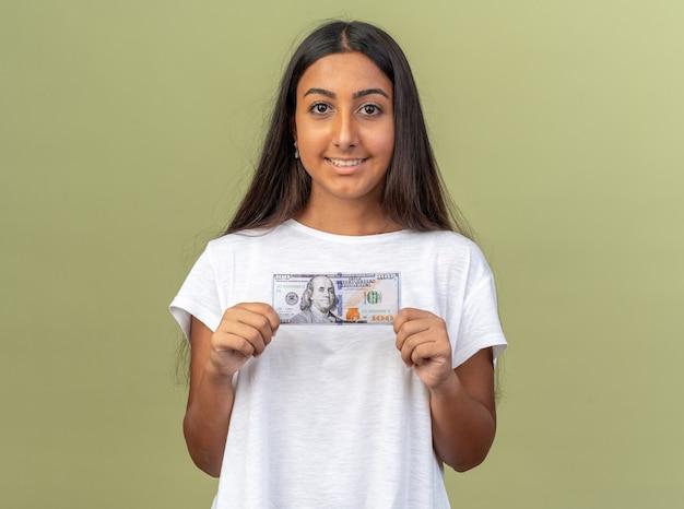 Gelukkig jong meisje in wit t-shirt met contant geld kijkend naar camera glimlachend zelfverzekerd over groen staan