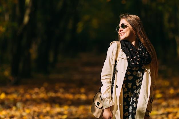 Gelukkig jong meisje in zonnebril met een zoete glimlach in jas en een warme herfst sjaal op zonnige dag.