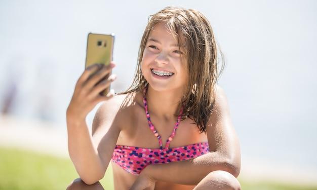 Gelukkig jong meisje met beugels die selfie maken op het strand in een warme zomerdag.