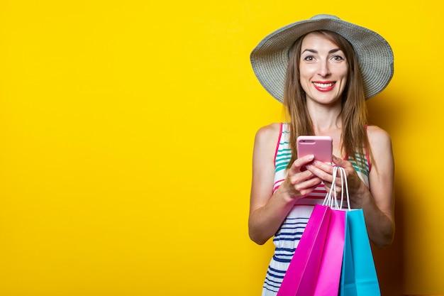 Gelukkig jong meisje met de pakketten van een telefoonholding met aankopen