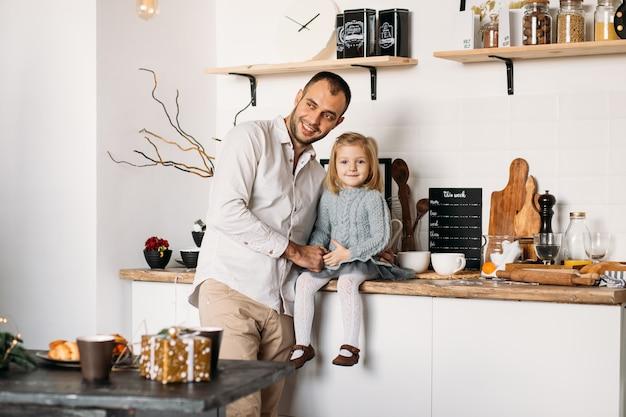 Gelukkig jong meisje met haar vader in keuken thuis.