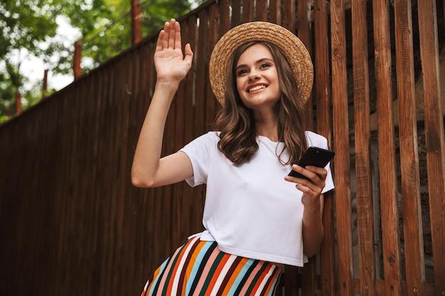 Gelukkig jong meisje met mobiele telefoon terwijl staande op de houten muur buitenshuis, hand zwaaien