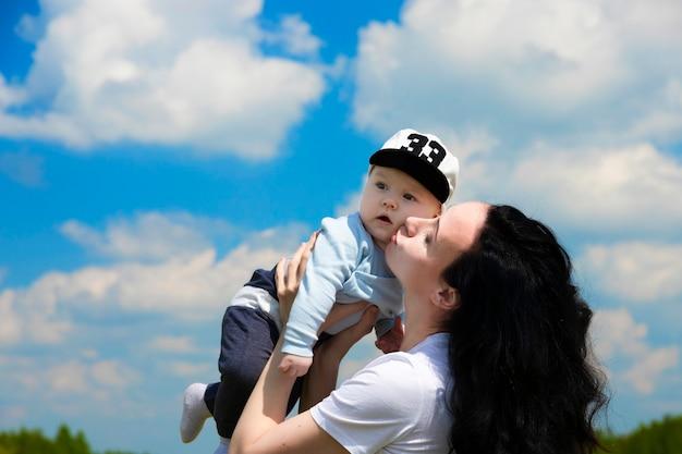 Gelukkig jong meisje, moeder speelt met haar baby in haar armen tegen een muur van blauwe lucht met wolken. ruimte kopiëren.