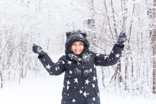 Gelukkig jong meisje overgeven een sneeuw in een winter woud