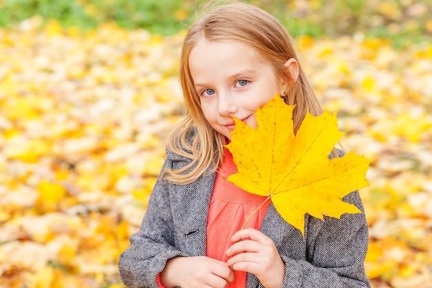 Gelukkig jong meisje speelt met vallende gele bladeren