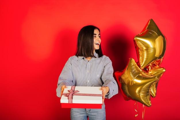 Gelukkig jong meisje viert haar verjaardag, met rode doos met cadeau, in de buurt zijn gouden ballonnen, rode achtergrond.