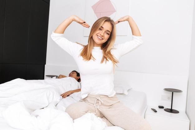 Gelukkig jong meisje zittend op bed in de ochtend, handen uitrekken