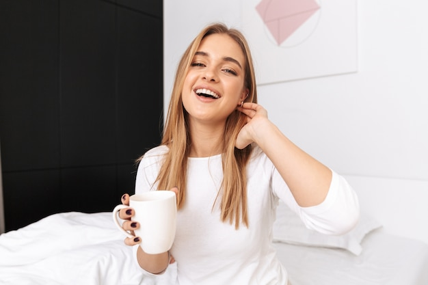 Gelukkig jong meisje, zittend op bed in de ochtend, met een kopje