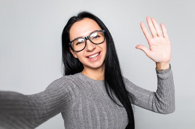 Gelukkig jong meisje zwaaiende hand naar camera terwijl het nemen van een selfie met mobiele telefoon geïsoleerd over grijze muur