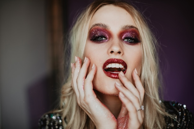 Gelukkig jong model met trendy make-up die goede emoties uitdrukt. binnenfoto van bevallige blanke vrouw met blond golvend haar.