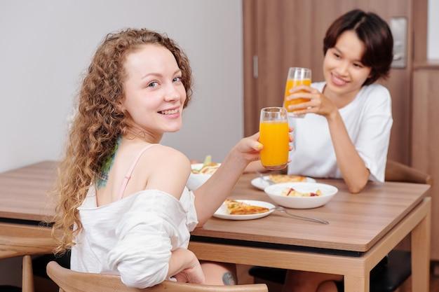 Gelukkig jong multi-etnisch lesbisch koppel dat verse jus d'orange drinkt tijdens het eten thuis