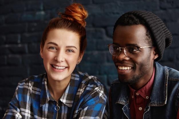 Gelukkig jong multi-etnisch paar ontspannen binnenshuis, praten, lachen om grappen en genieten van elkaars gezelschap. leuke gembervrouw in geruit overhemd die bij koffiezitting rusten dichtbij de modieuze zwarte mens
