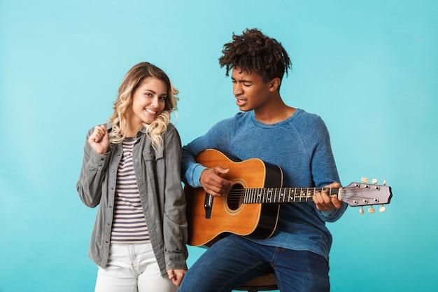 Gelukkig jong multiethninc paar dat samen een gitaar speelt die over blauwe muur wordt geïsoleerd