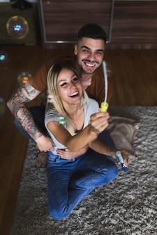Gelukkig jong paar dat blazend de bellen op deken geniet van