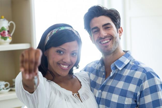 Gelukkig jong paar dat een sleutel van hun nieuw huis toont