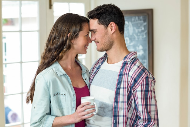 Gelukkig jong paar dat elkaar omhelst en een kop van koffie in woonkamer heeft