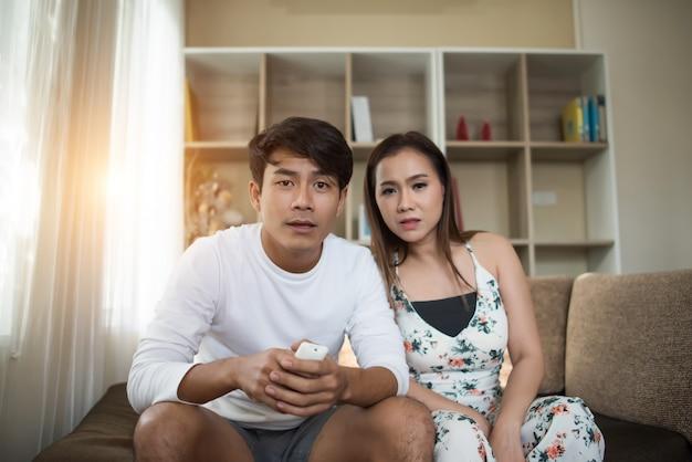 Gelukkig jong paar dat en op tv ontspant kijkt bij woonkamer