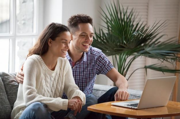 Gelukkig jong paar dat lettend op grappige video lacht of videocall maakt