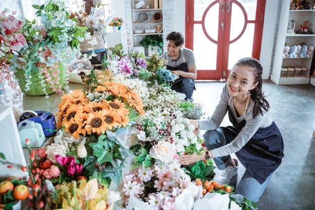 Gelukkig jong paar dat schort draagt die voorwaardebloem controleert die in bloemenwinkel werkt