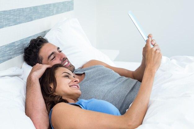 Gelukkig jong paar dat tablet gebruikt terwijl het liggen op bed